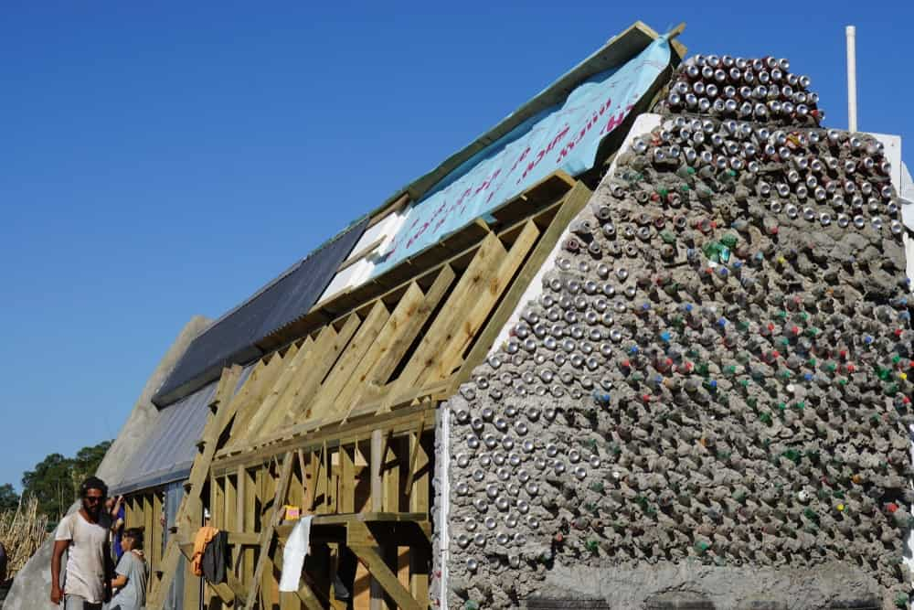 This is a close look at an earthship under construction with a alrge wall made of plastic bottles and cans.