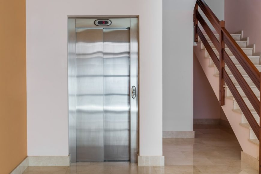 This is an elevator at an apartment building by the stairs.