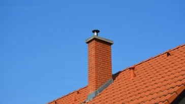 A close look at a red brick chimney with flashing.