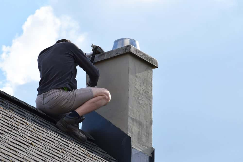 A man on the roof of the house installing chimney flashing.