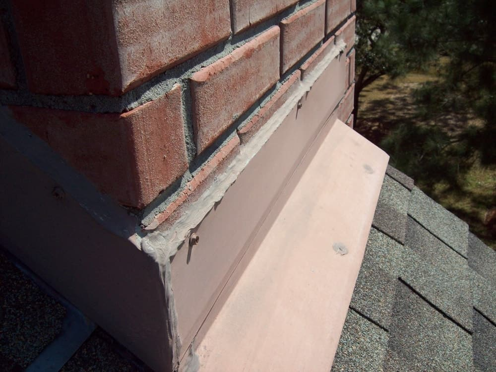 This is a close look at a red brick chimney with flashing.