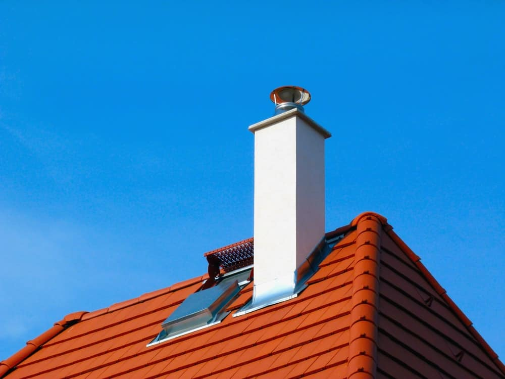 This is a white chimney with flashing on a red tile roof.