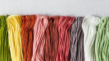 A close look at a row of various colorful threads on a canvas.