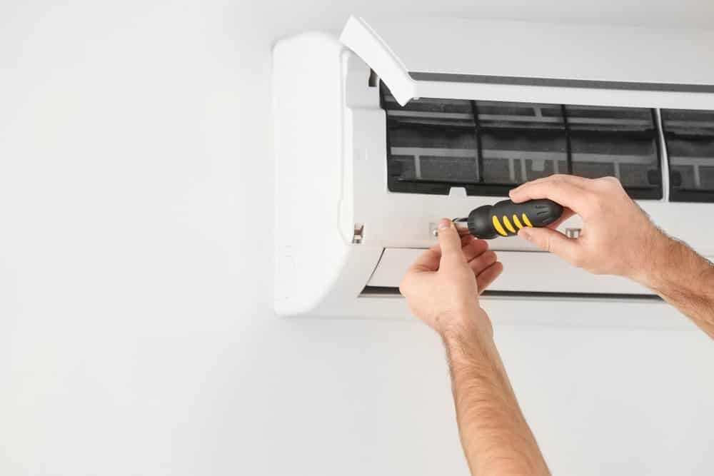 A man in the process of repairing a wall-mounted split-type air conditioner.