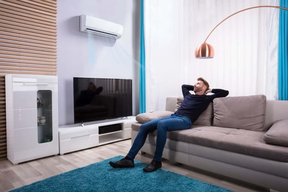 TV'nin üzerine monte edilmiş klima ile konforlu hale getirilen oturma odasında dinlenen bir adam.