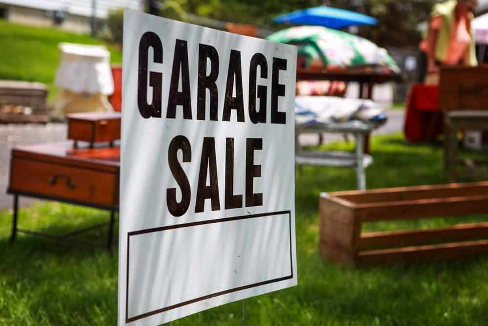 A close at the signage for the garage sale in the background.