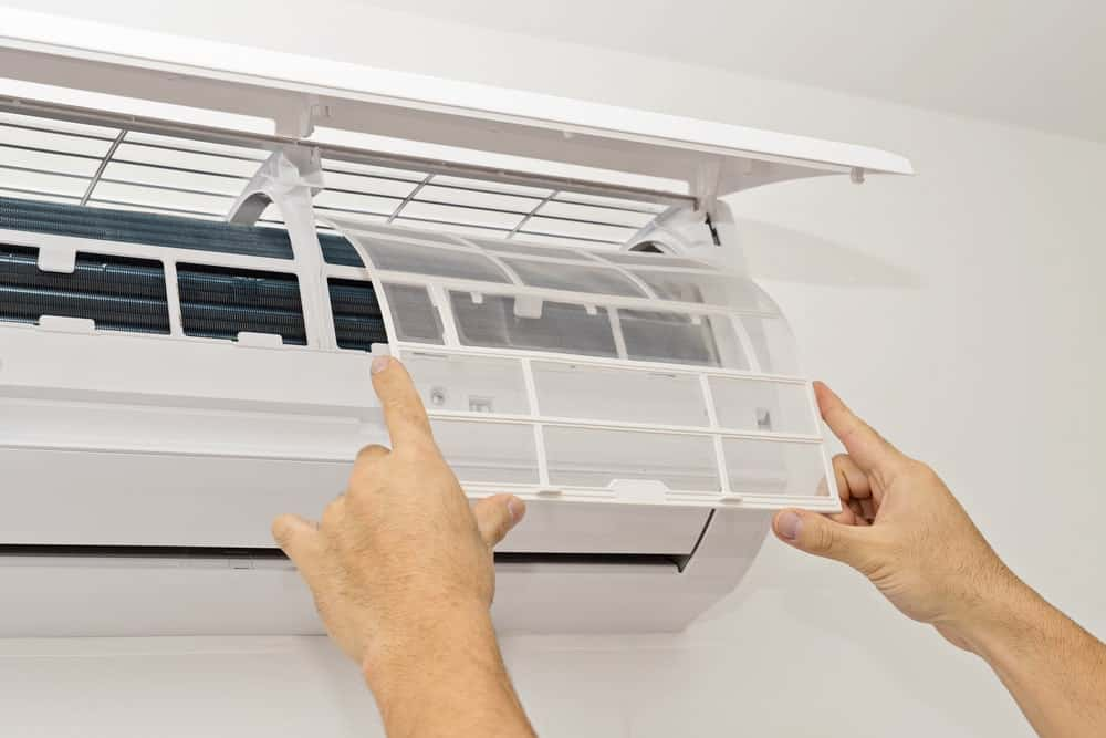 A man in the process of changing the filters of a wall split-type air conditioner.