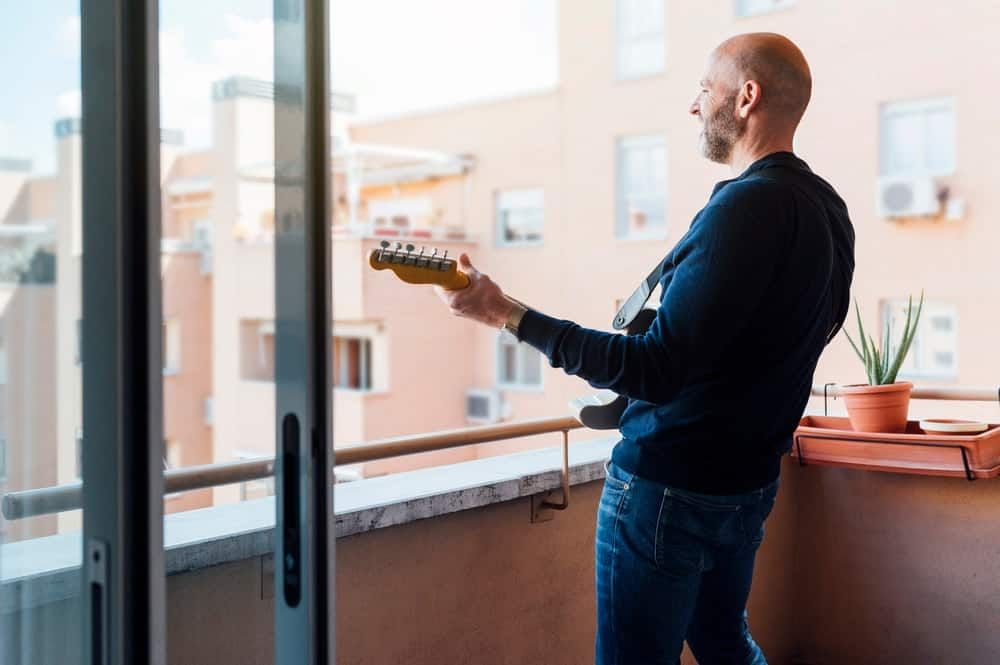 A man playing the guitar in his balcony.