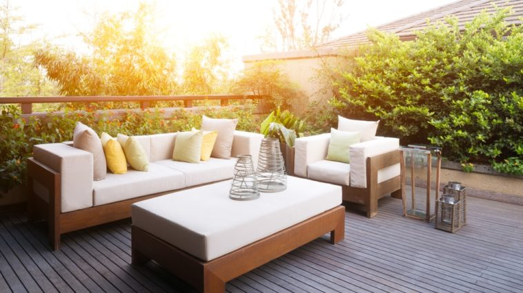 This is an outdoor patio with a wooden deck floor and a wooden outdoor sofa set with cushion.
