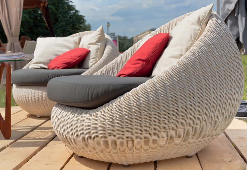 This is a close look at a couple of comfortable woven wicker outdoor furniture with cushion.