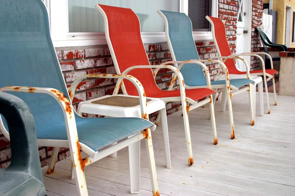 A row of rusty outdoor chairs on a patio.