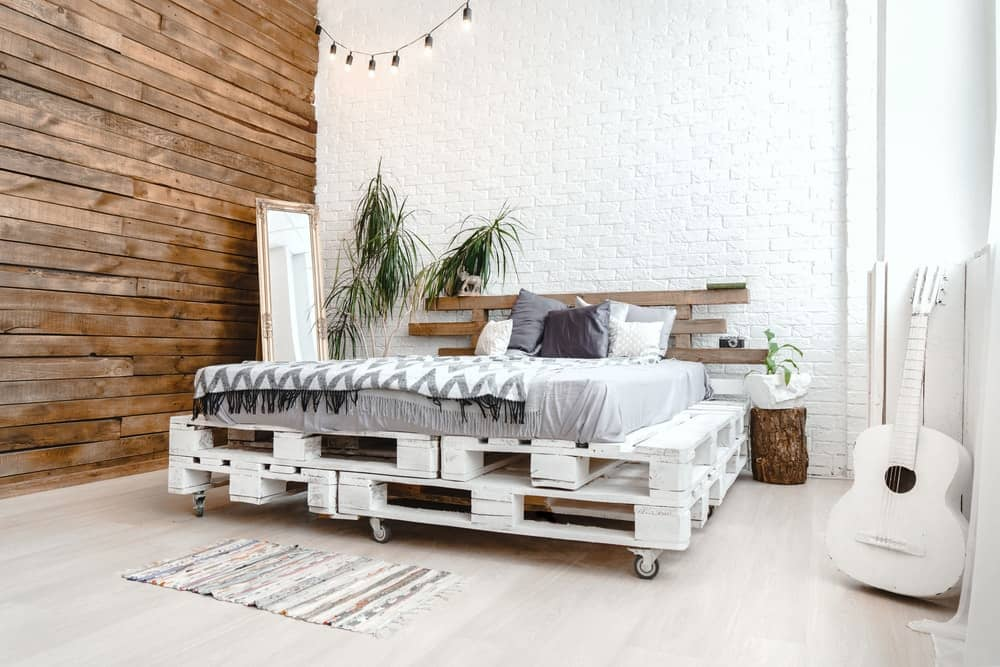 This bedroom has a rustic wooden bed frame made of wooden pallets.