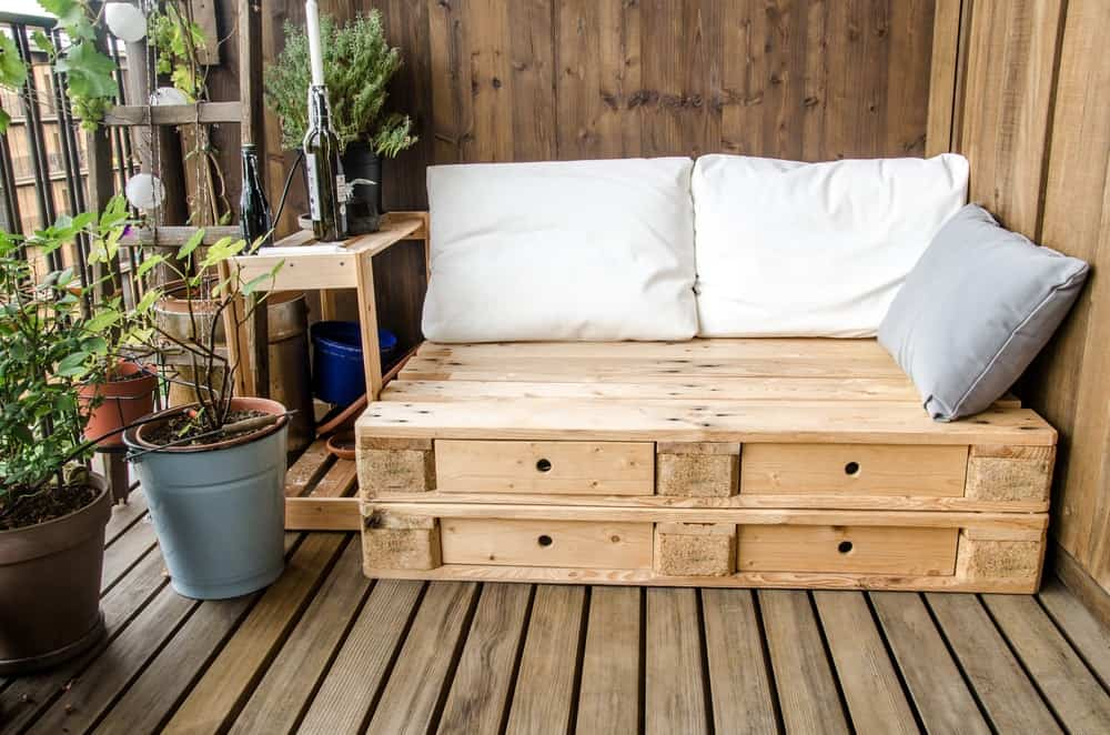 This is a wooden deck terrace with a wooden bench made from wooden pallets.