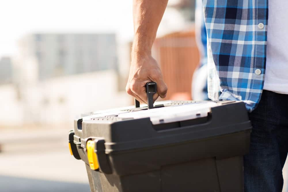 This is a close look at a man carrying a large black toolbox.