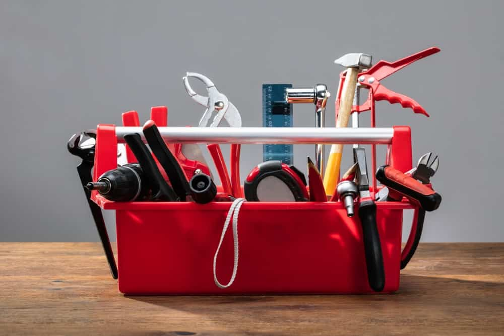 This is an open toolbox with handle filled with tools.