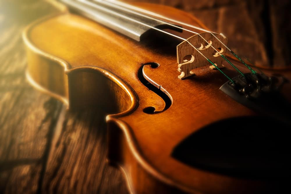 A close look at a vintage-style wooden violin on a wooden surface.