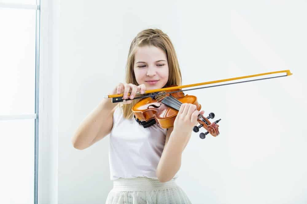 A girl playing the violin inside a bright and white room.