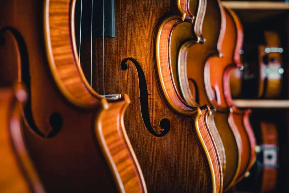 A close look at a row of vintage-style violins on display.