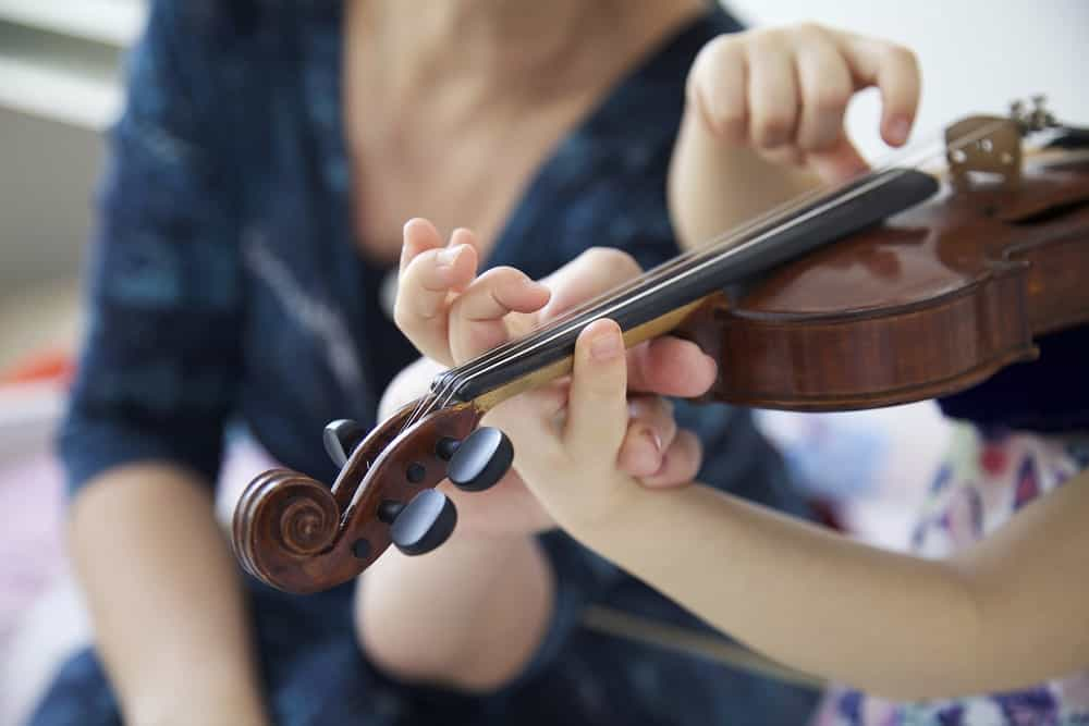 This is a close look at a woman teaching a girl how to play the violin.