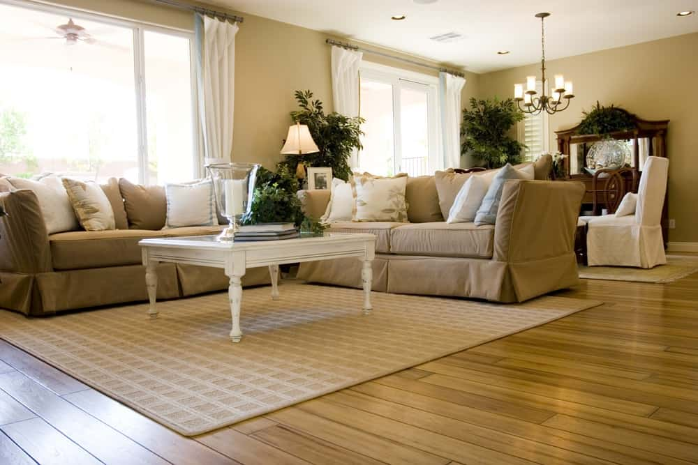 A close look at a living room with a couple of beige sofas to match the beige area rug.
