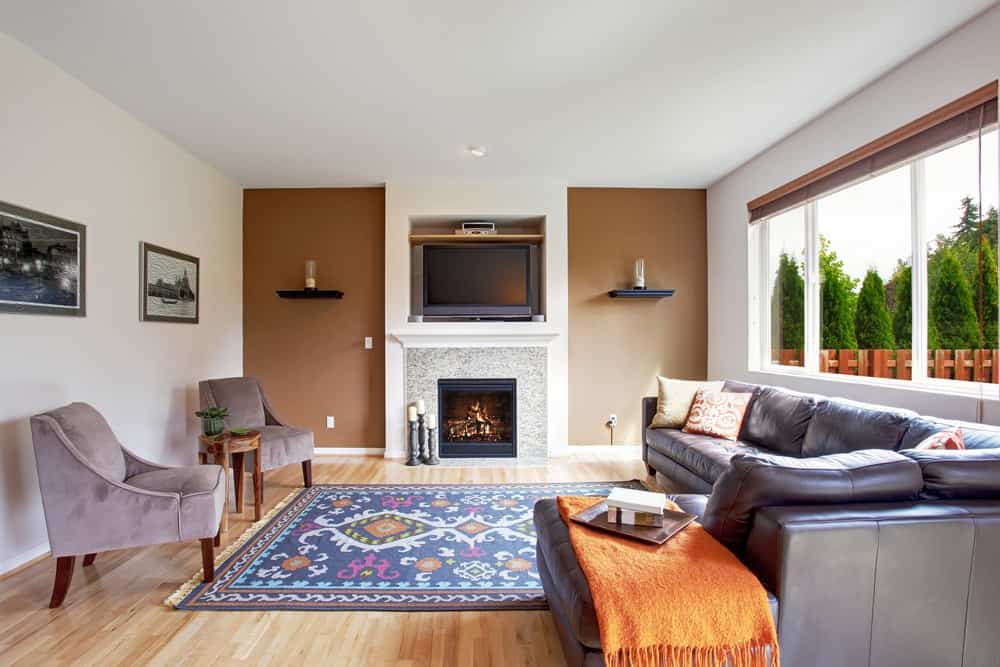 A look at a living room with a colorful patterned area rug across from the fireplace.