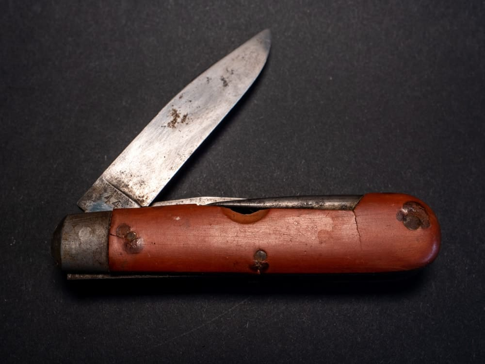This is a vintage pocket knife with a wooden handle and a rusty blade.