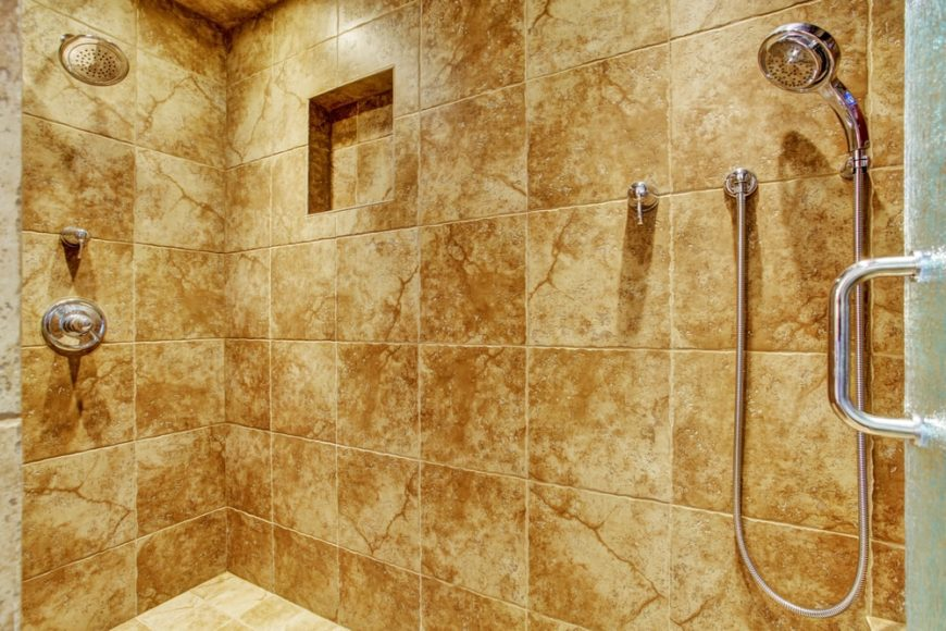 This is a close look at a bathroom's shower area with granite tiles.
