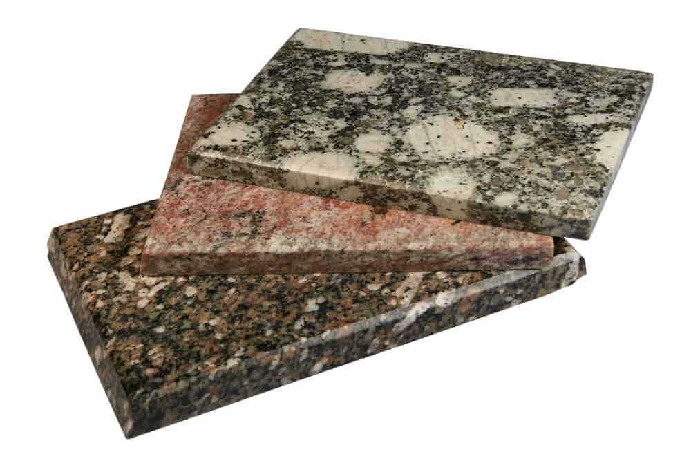 Pieces of granite tiles on a white surface.