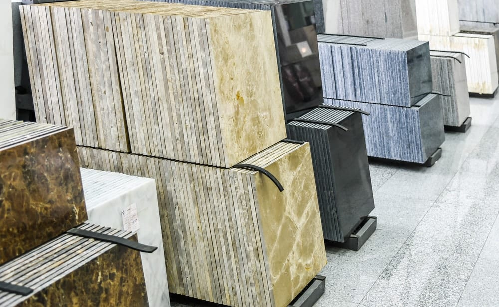 Stacks of different granite tiles on display at a store.