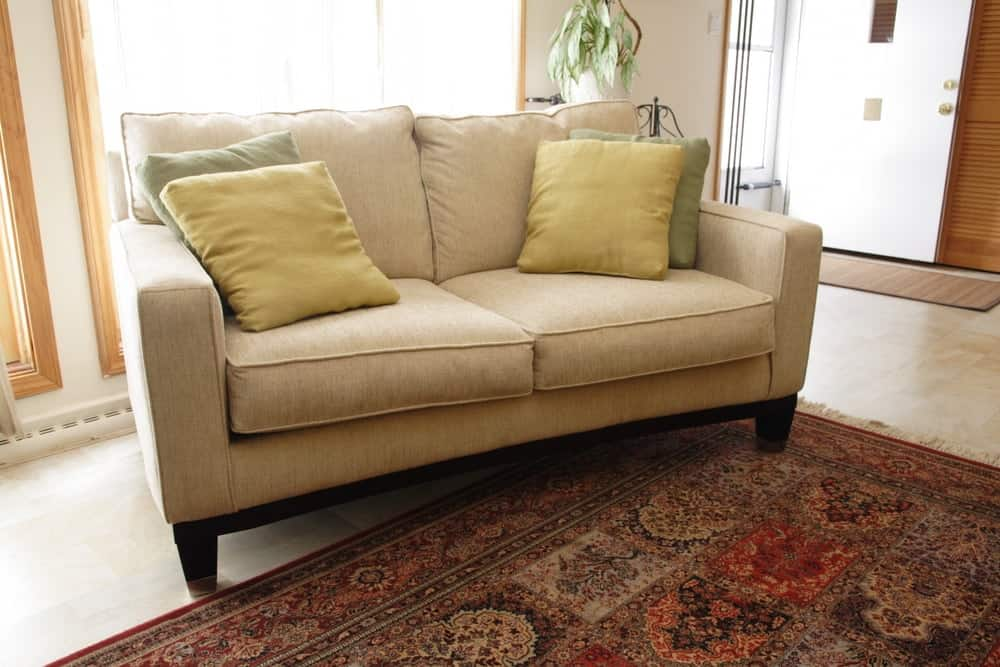 A comfortable beige loveseat by the entrance of the house.