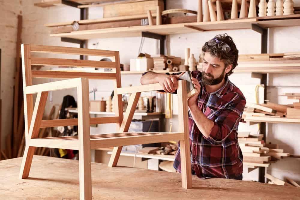A close look at a carpenter in a furniture workshop making a chair.