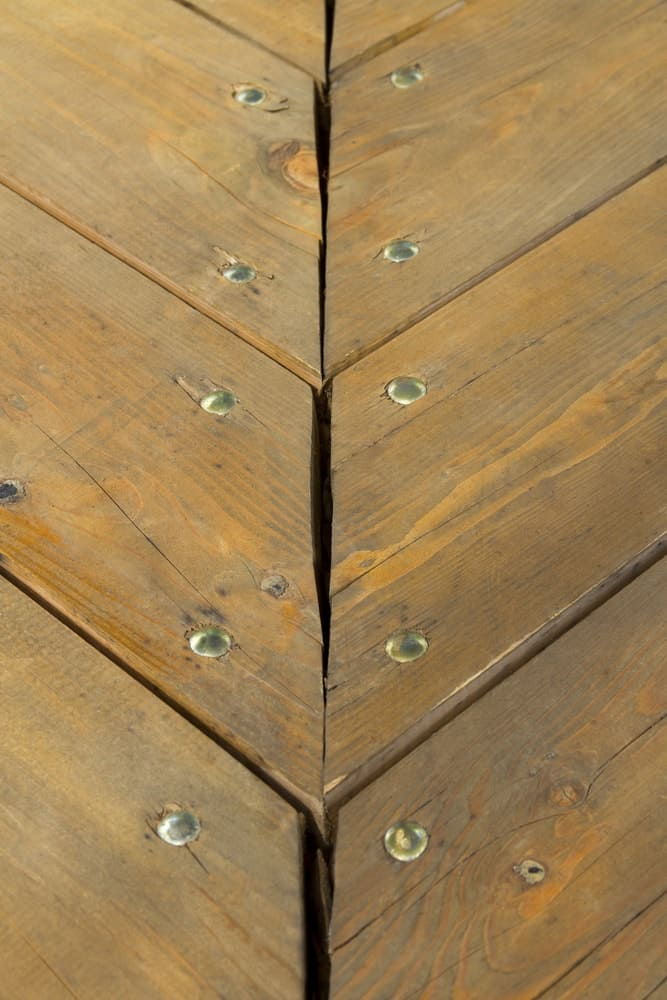 This is a close look at a floor with miter wood joinery using metal pins.