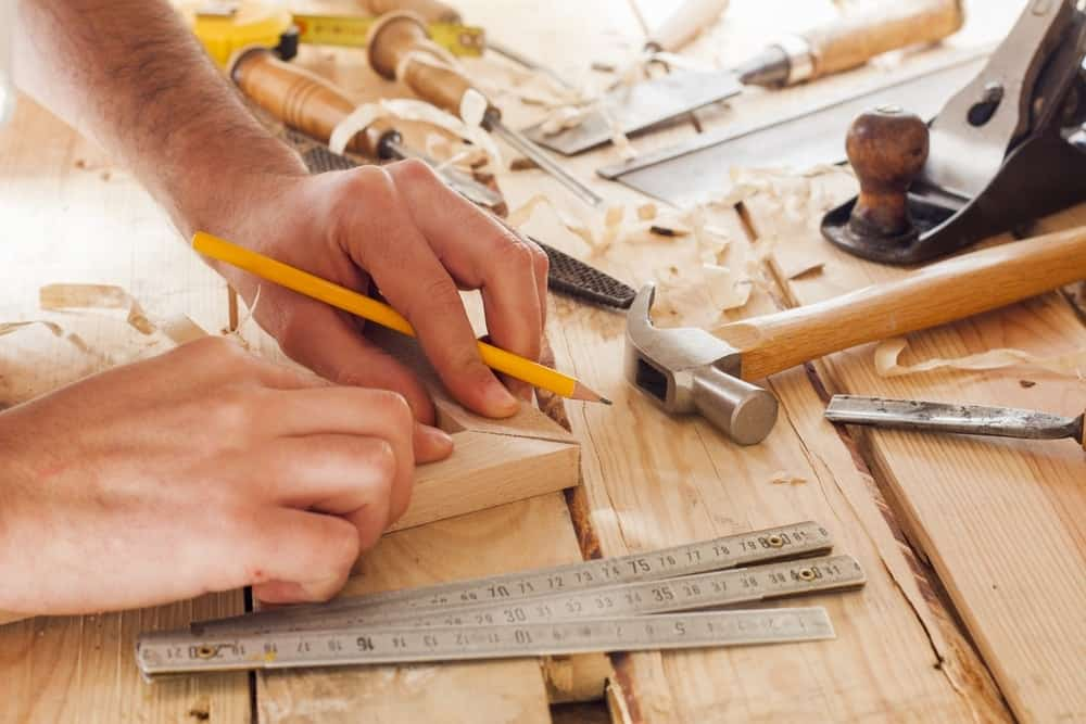 A man doing a miter joint with two pieces of wood by hand.
