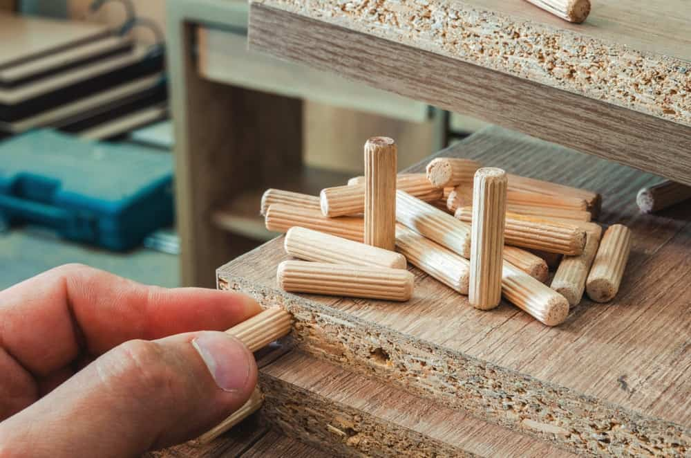 A close look at a man inserting furniture fittings made of wood.