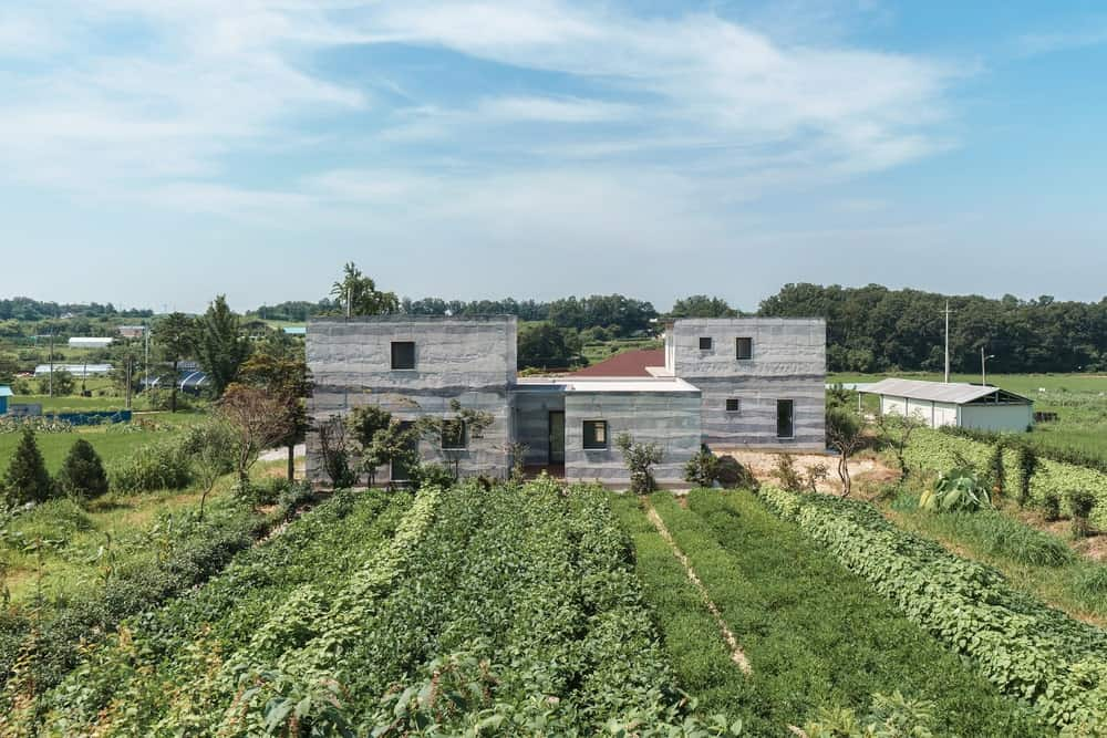 This is an aerial view of the property on the north-east side of the house showcasing the gray concrete tone of the exteriors that stand out against the green landscape.