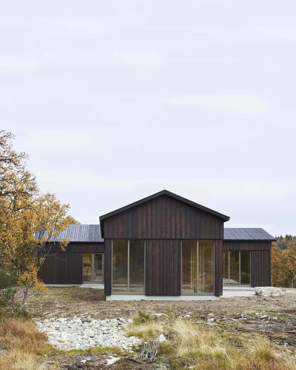 This is a look at the exterior of the house that has dark wooden tones to its exterior walls paired with glass walls.