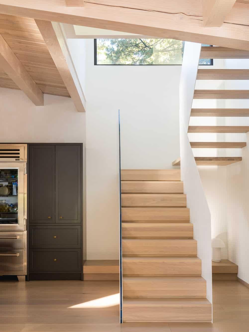 This is a closer look at the staircase that has light wooden steps to match the hardwood flooring contrasted by the dark tone of the kitchen cabinetry.