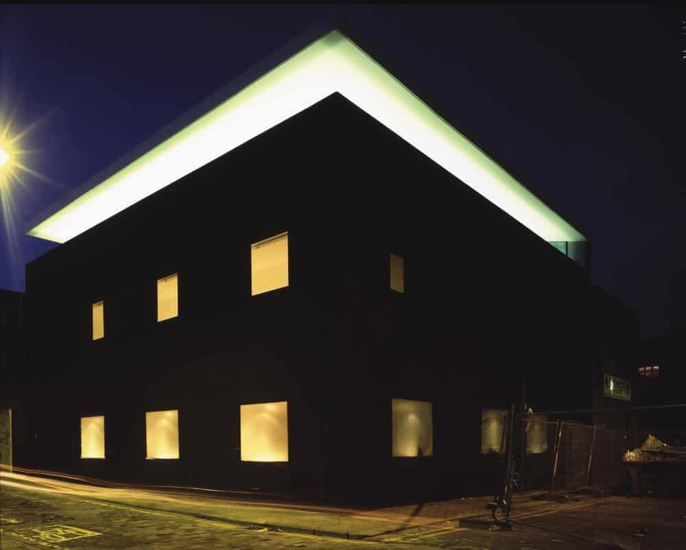 This is a nighttime view of the house showcasing the warm glow of the windows and the top floor glass wall giving the house a unique look.