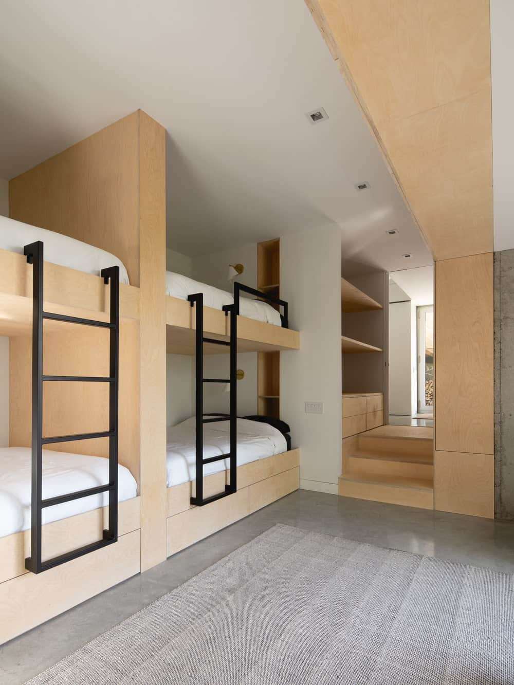 The bunk bedroom has a large wooden structure with four beds and attached two wrought iron ladders.