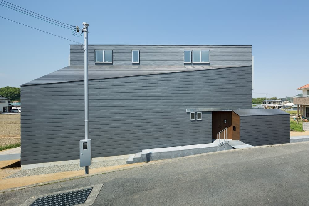 This is a look at the front of the house with a unique shape showcasing the main entrance.