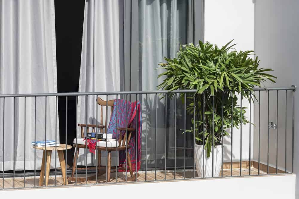 The wooden chair on the balcony is paired with a small stool that can serve as coffee table and footstool.
