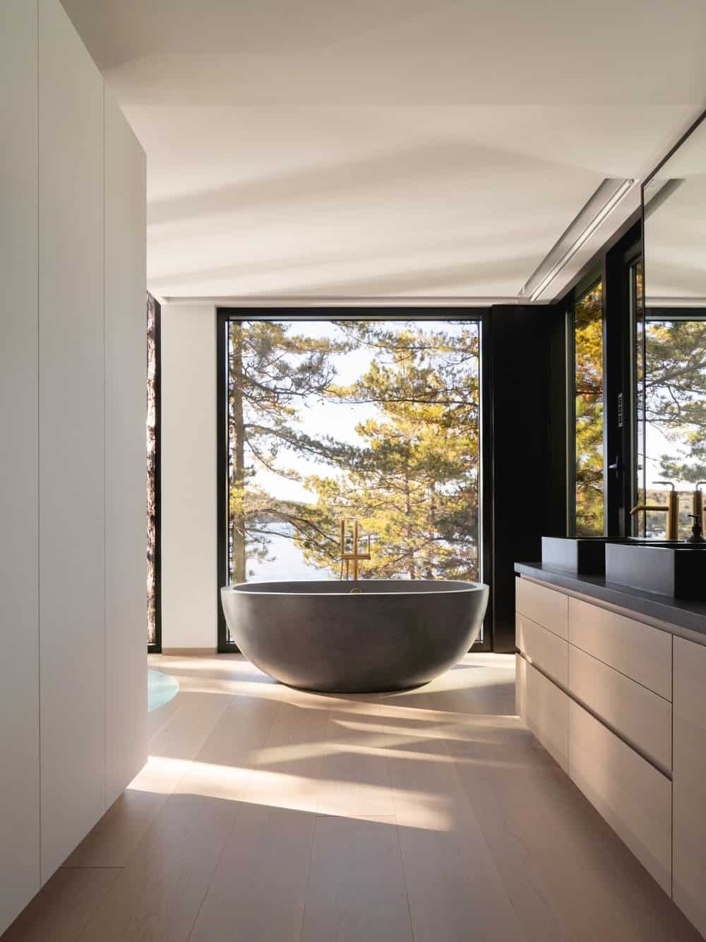 The bathroom has a large freestanding bathtub standing by the glass walls at the far end of the modern vanity.