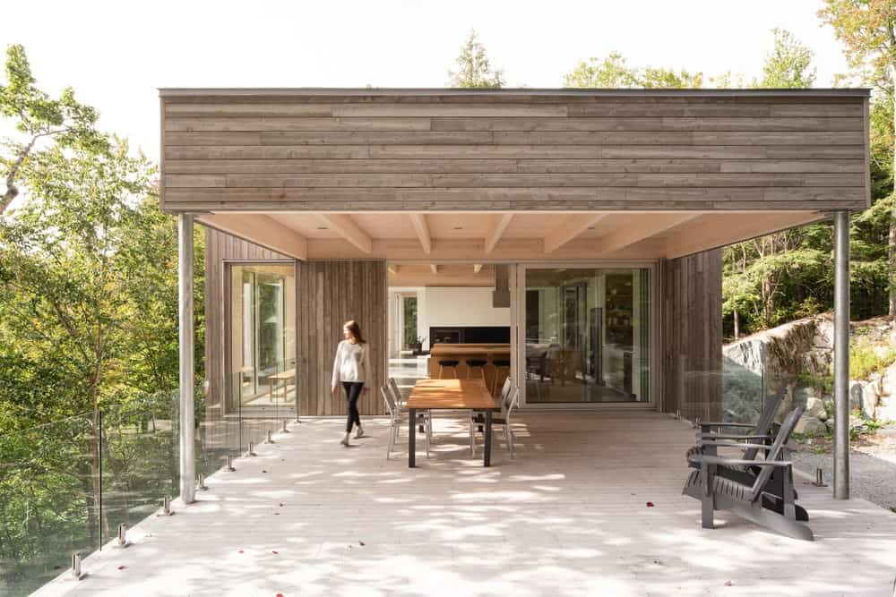 This is the covered area that is fitted with an outdoor dining area with a view of the forest beyond.