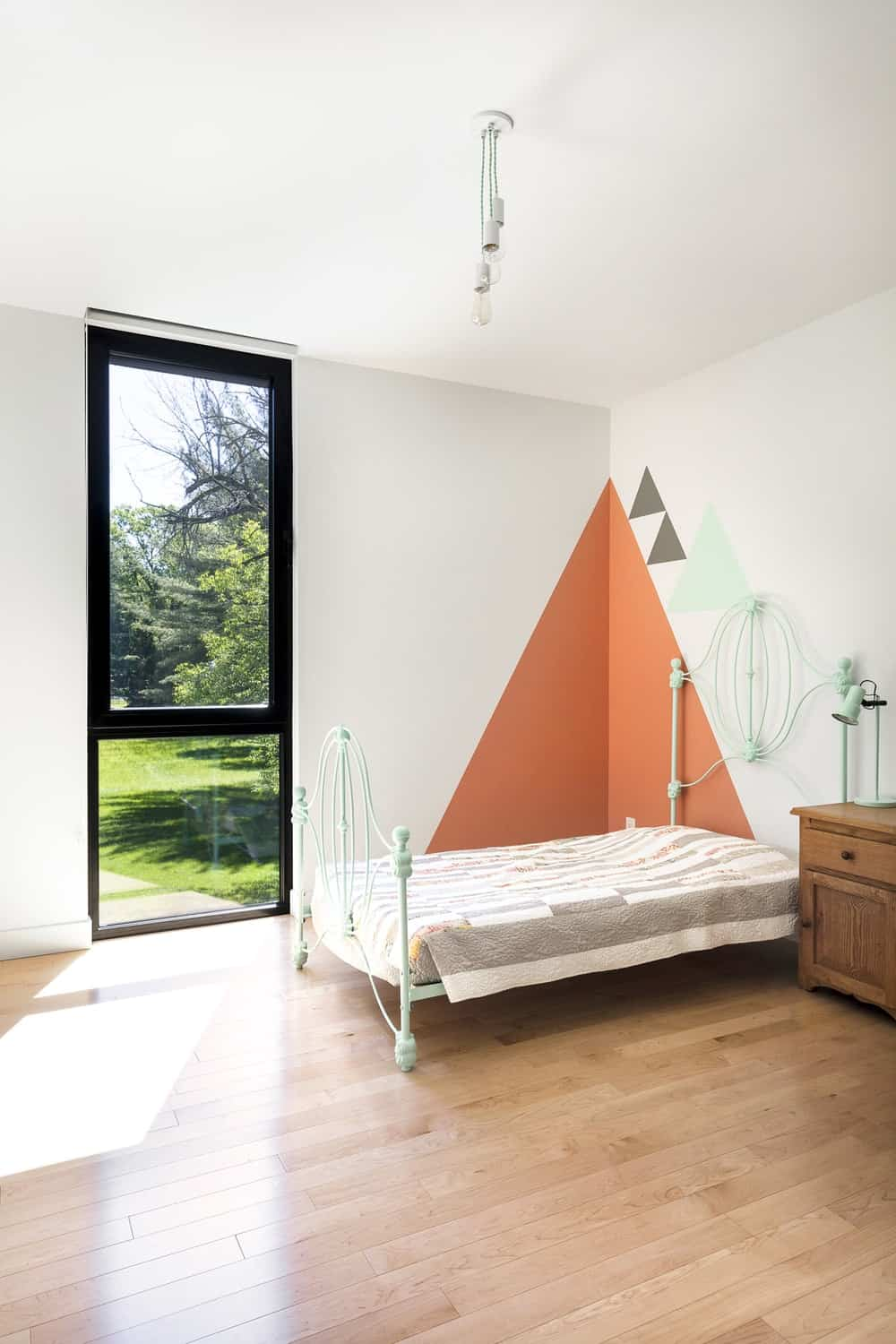 This is the simple kid's bedroom with a pastel-toned four-poster wrought-iron bed at the far corner by the tall window paired with a wooden bedside drawer bearing a table lamp of the same tone as the bed.