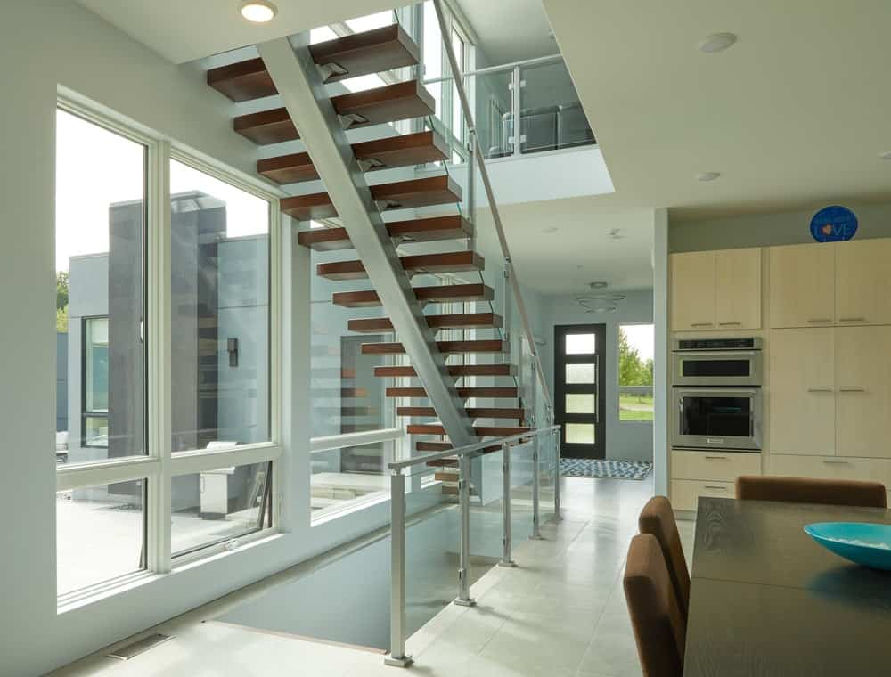 Underneath this set of stairs is another set with the same design. On the far side is the main door of the house with its main door that has glass panels.
