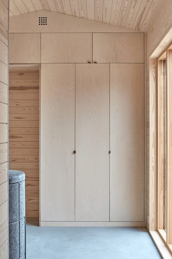 This is a close look at the corner of the house that has built-in cabinets making it stand out against the shiplap walls with its simple design.
