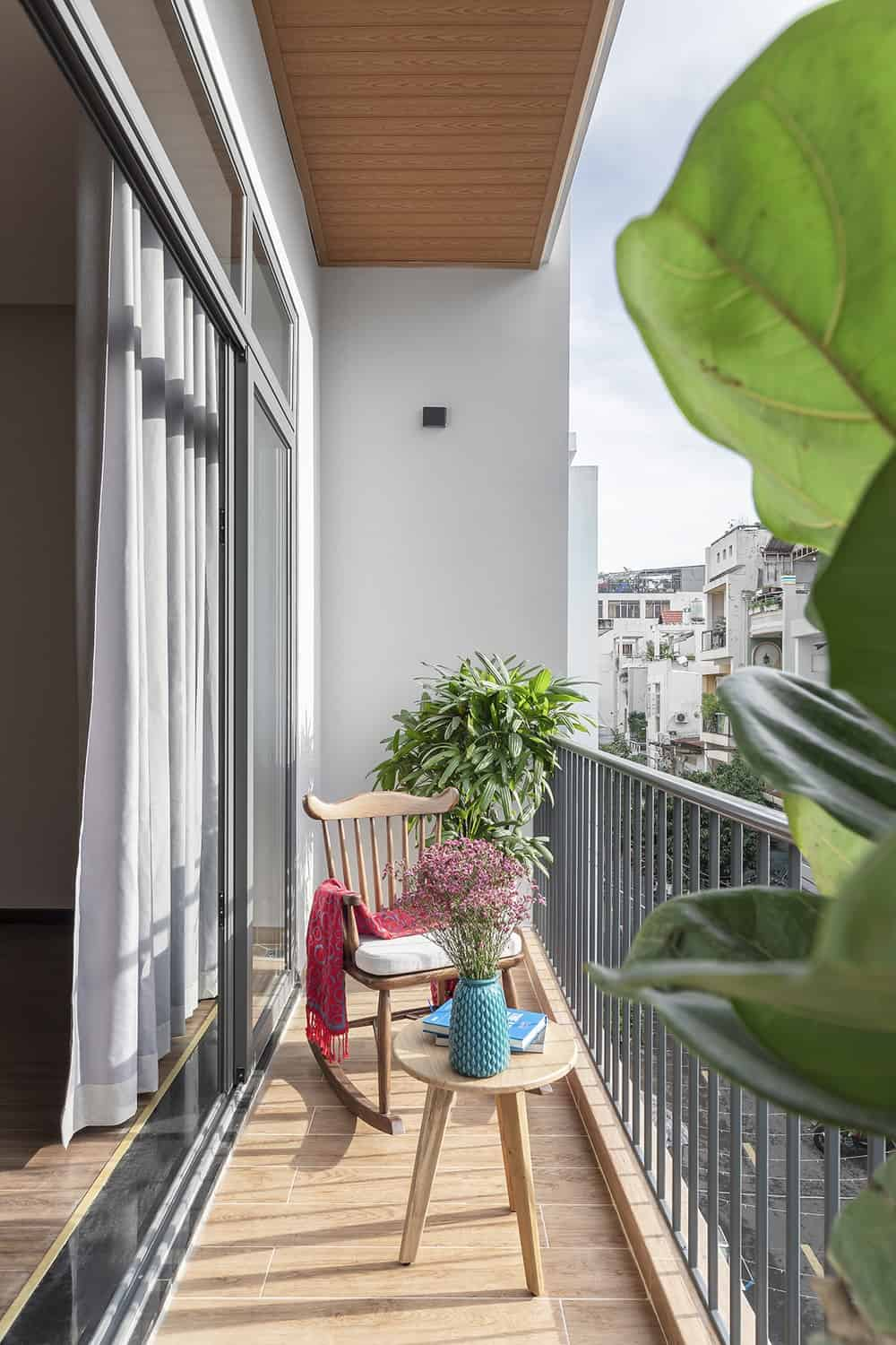 This view of the balcony showcases the size of the area that can only fit one wooden chair and a wooden coffee table.