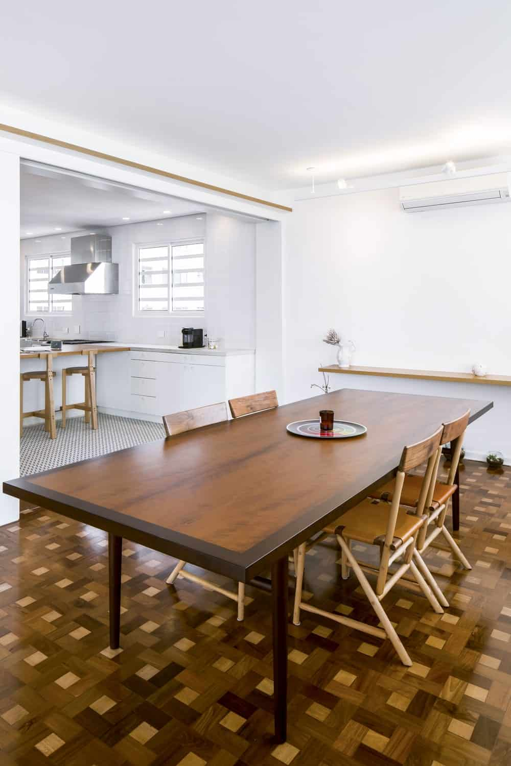 This is a closer look at the large rectangular dining table surrounded by simple chairs.