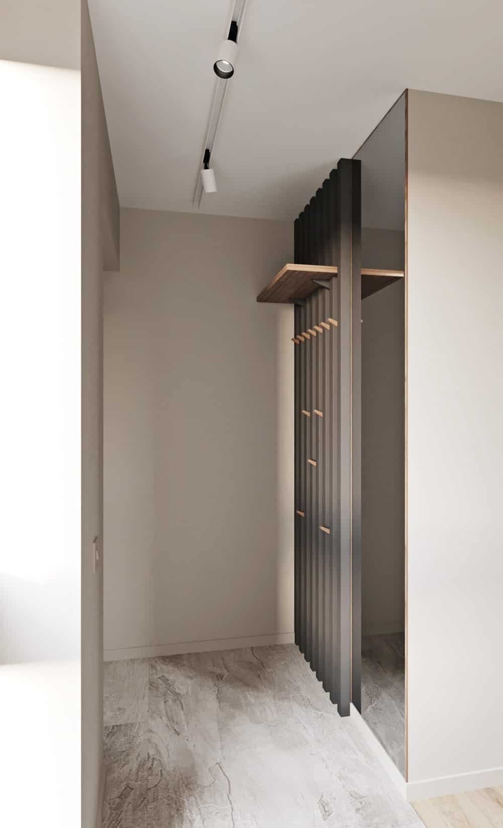 This is a close look at the house's mudroom with a simple dark gray wooden panel with wooden hooks for the jackets and hats. This is topped with a wooden floating shelf and a mirror on the side.