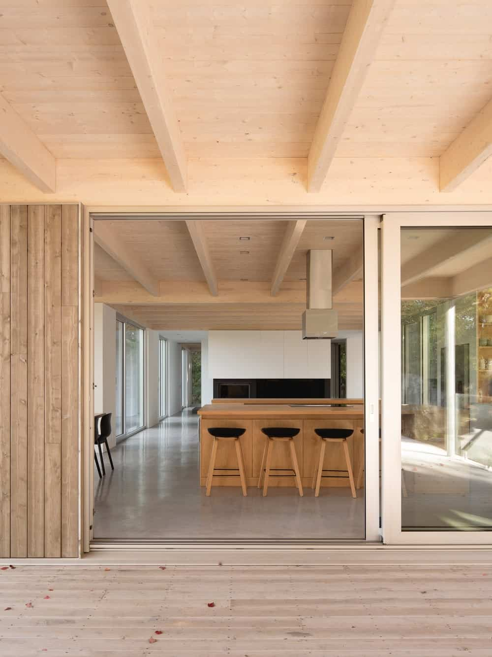 From the covered patio are the sliding doors that lead to the kitchen with a wooden beamed ceiling.